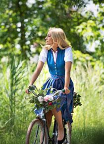 Blonde Frau im Dirndl fährt Fahrrad